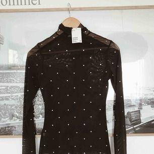 En svart tröja i mesh, helt ny med lappar kvar. Frakt tillkommer
