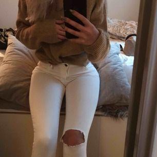 Ett par vita jeans med hål i. Frakt tillkommer