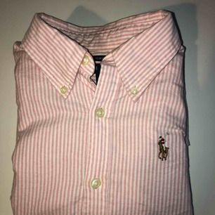 Ralph Lauren skjorta med vit/rosa ränder i jättebra skick! Endast använd ca 2 gånger. Den är helt felfri och har såå fin passform (det är en slim fit modell).