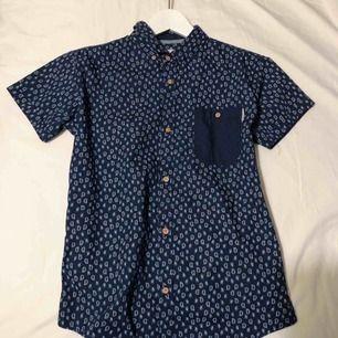 Skjorta köpt på second hand i London! Står att den är för killar 11-12 år men den passar även på mig som är tjej xs-s. Knapparna är gjorda i kork. Köpare står för frakt eller mötas upp i Karlstad💕