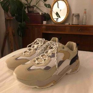 Ett par helt oanvända, coola, beiga sneakers från bershka med reflexdetaljer! Nypris 500. Frakt tillkommer💞