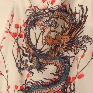 Vitt linne med drake på ryggen