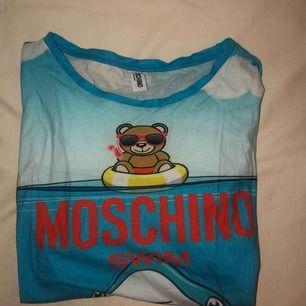 Supercool äkta Moschino-swim T-shirt. Inköpt i Italien för ca ett halv år sedan. Säljes pågrund av för stor! ANVÄND 0 GÅNGER
