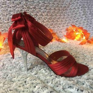 Röda sandaletter / pumps i satin, med söt rosett baktill och snygg silverfärgad klack. Endast använda ett fåtal gånger, sula och klack i perfekt skick. Stl.40