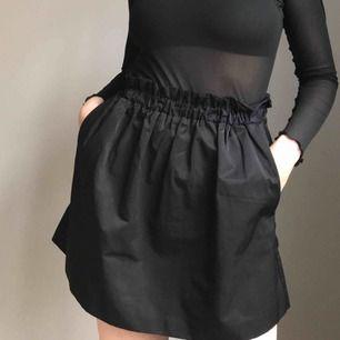 Svart kjol i tjockt, blankt material med volang upptill och fickor från Stradivarius • i storlek S men pga stretch i midjan kan den passa en M lika bra • i mkt fint skick! • frakt på 36kr tillkommer!