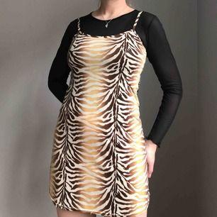 Djurmönstrad miniklänning i brun, gul och beige från LUCY Paris • ingen storlek men sitter som en S • tyget har små glansiga prickar, se sista bilden • bra skick! • frakt på 36kr tillkommer🐾