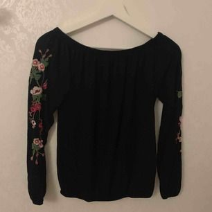 En söt blus som är svart med blommor på armarna 🌸💟