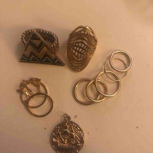 guldfärgade ringar samt en guldig berlock föreställande en segelbåt. bestäm priset själv