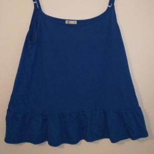 Blus /linne I klarblå färg med volang nedtill   Tunna justerbara axelband Frakt betalas av köparen