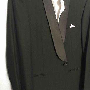 Svart kostym  Kavaj: bred på axlar 45cm Under armhål till sida 53 cm gånger 2 Längd:74cm Kjortan: i strl 3 Bred på axlar 50 cm Under armhål till andra 55gånger 2 Längd: 74 cm Byxan: i strl 50 Längd: 100cm In mellan ben ner 74cm Rund midja 90 cm