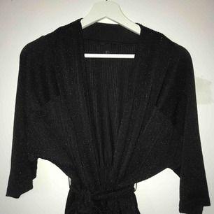 Svart kort kimono med skimrande effekt, storlek S. Använd få tal gånger, har då matchat med svart spetsbh!