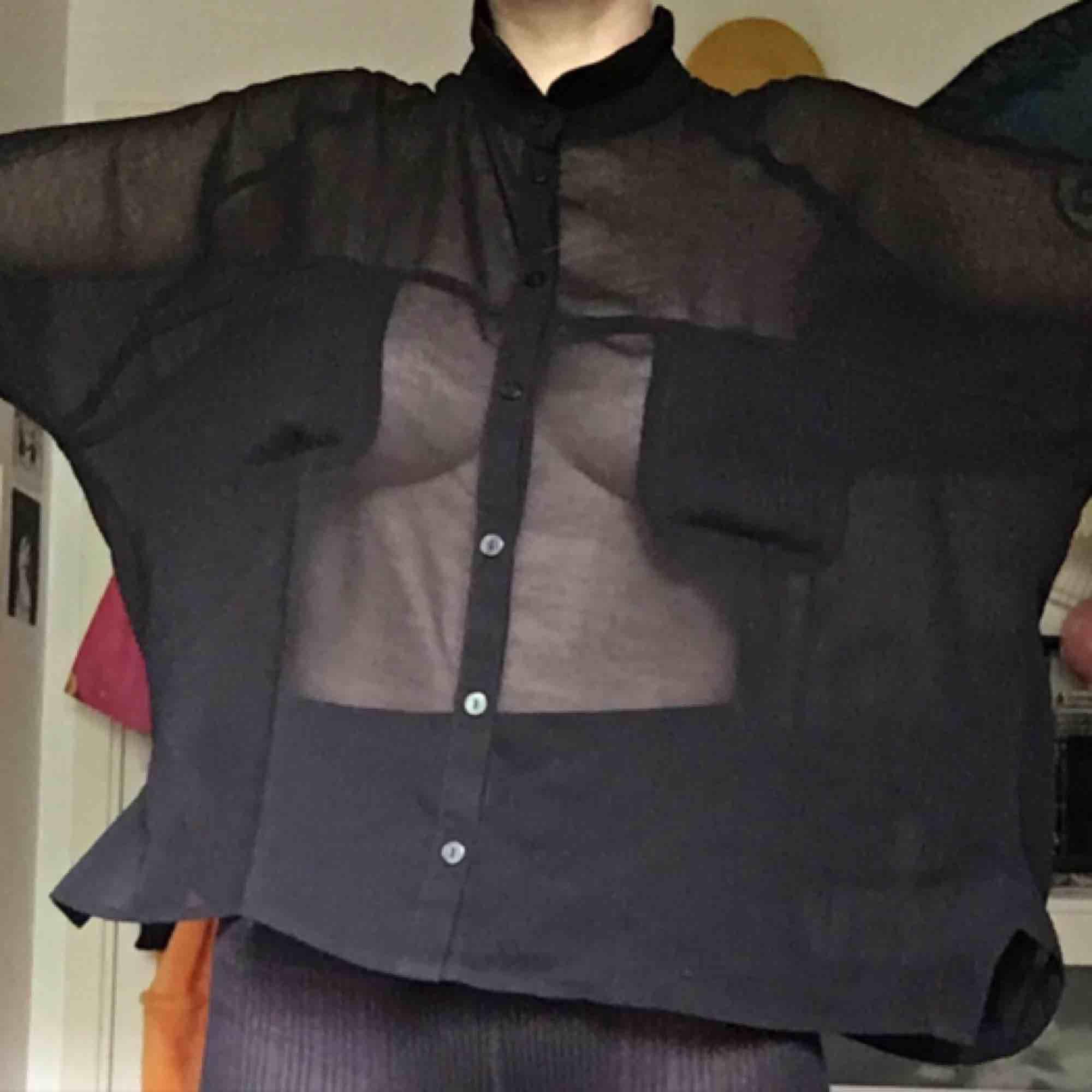 Transparent svart skjorta. Dessvärre har den mindre hål (endast dom som syns på bild) men det tänka inte på när en har på sig den och går säkert att laga. Passar från xs-medium . Blusar.