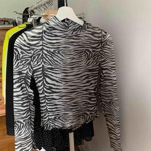 Zebramönstrad tröja i tyll, långa ärmar och halv polo. Jätte snygg att ha under en tröja eller med en bralette, använd 1 gång :)