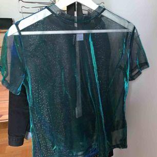 Halv oversized t shirt i glittrigt tyll. Blå/grön färg. Använd 1 gång. Köpare står för frakt