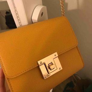 Skitsnygg, gulaktig handväska med gulddetaljer.