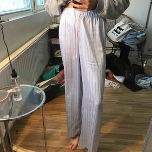 Ett par blåa pyjamasbyxor med beiga detaljer. Det står stl XS men skulle säga att d oxå passar S o M