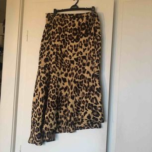 Helt oanvänd leopardkjol i tunt tyg. Lite volangig och snedskuren nedtill i modellen, blixtlås i sidan.  Frakt tillkommer!