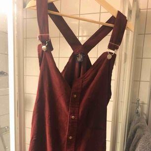 Hängselklänning från beyond retro label. Väldigt bra skick, reglerbara hängselband. Kort, snygg med jeans under! Vinröd manchester