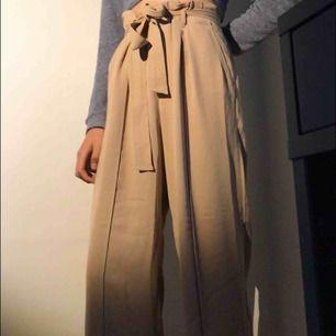 Beiga kostymbyxor från bikbok. Är själv stl S och det funkar också bra därför att det finns ett band att knyta runt