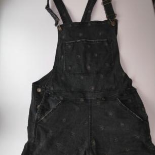 Shorts hängselbyxor I svartgrå denim från Drop Dead storlek m från UK. Broderade pentagram I guldaktig färg. Slitage längs benen och kanterna är så med flit inte gjorda av mig. Vill ni ha fler bilder så fråga bara 😊