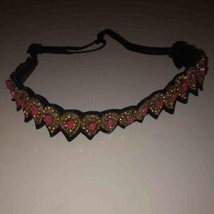 Ett pannband med bohemisk stil, samt med fina pärlor. Den är justerbar med hjälp av ett spänne.