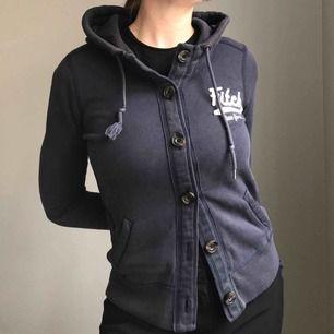 Mörkblå mjuk tjocktröja med luva och knappar framtill från Abercrombie & Fitch i storlek M • i använt skick vilket ger den en härlig retro-look! Frakt på 54kr tillkommer