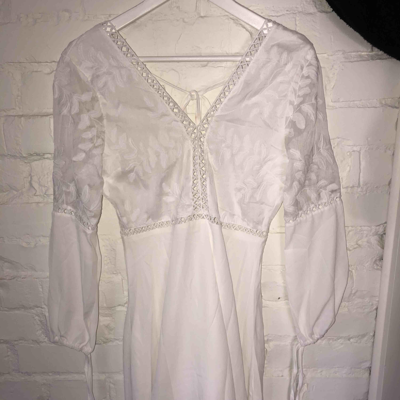 Ännu en jättefin vit klänning men öppen rygg perfekt till studenten. Lite liten i storlek men är i gott skick med fint tyg. Bild 1- framsidan Bild 2- baksidan. Klänningar.
