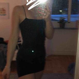 En svart tajt klänning med tunna band ifrån Gina🥰