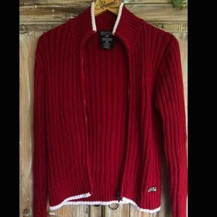 Stickad röd Polo Ralph Lauren kofta med dragkedja i fram. Vita accenter längst ner, samt vid kragen och vid ärmarna. Väldigt fint skick, nästan oanvänd.