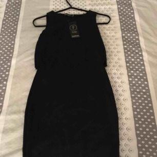 """ALDRIG ANVÄND! """"Petite Holly double layer scalfop hem dress"""" kort super söt klänning från boohoo med """"vågiga kanter"""". Säljes p.g.a. fel storlek. Kan mötas upp i centrala Uppsala, annars betalar köparen frakt :)"""