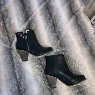 Svarta högklackade skor med guldetaljer