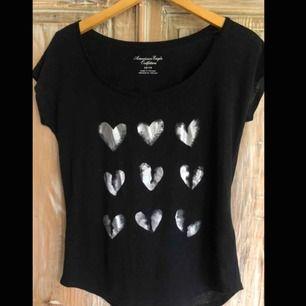 Svart American Eagle t-shirt med silvriga hjärtprint. Står storlek XS i, men passar upp till M. Frakt ej inkluderat.