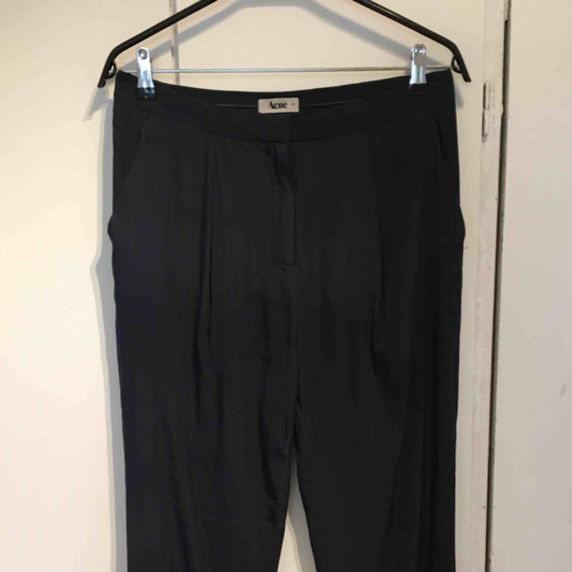 Duvblå byxor i 100% polyester. Loose fit. Laserskurna nertill. Har använt dem en del därav det låga priset. Inga hål eller fläckar, säljes i befintligt skick! . Jeans & Byxor.