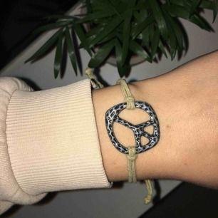 Justerbart armband med peace-märke. Jättefint, knappt använt. Frakt ingår i priset.
