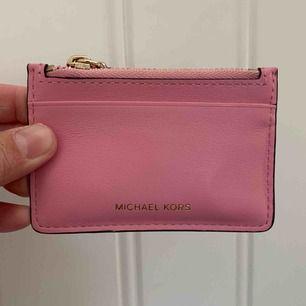Äkta michael kors plats för  kort och mynt för dig som inte gillar stora plånbok är detta perfekt. Denna hör egentligen till min plånbok men tycker inte jag behöver den alls äkta såklart. frakt ingår. fint skick då den är aldrig använd.