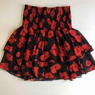 Röd svart kjol med blommor. Volang och stretchig midja. Jätte fin på sommaren