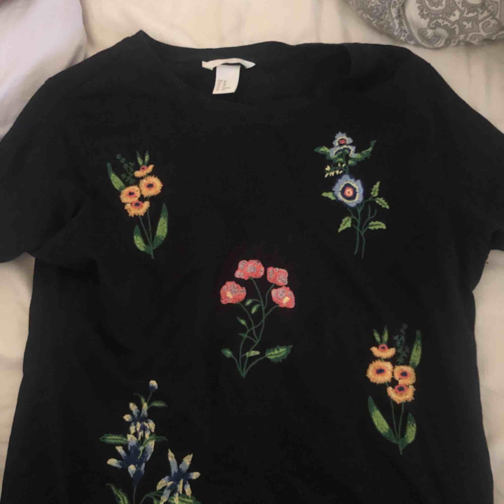 Superfin t-shirt från H&M med blommig brodyr på. Endast använd en gång därav nyskick. Frakt ca 20 kr. T-shirts.