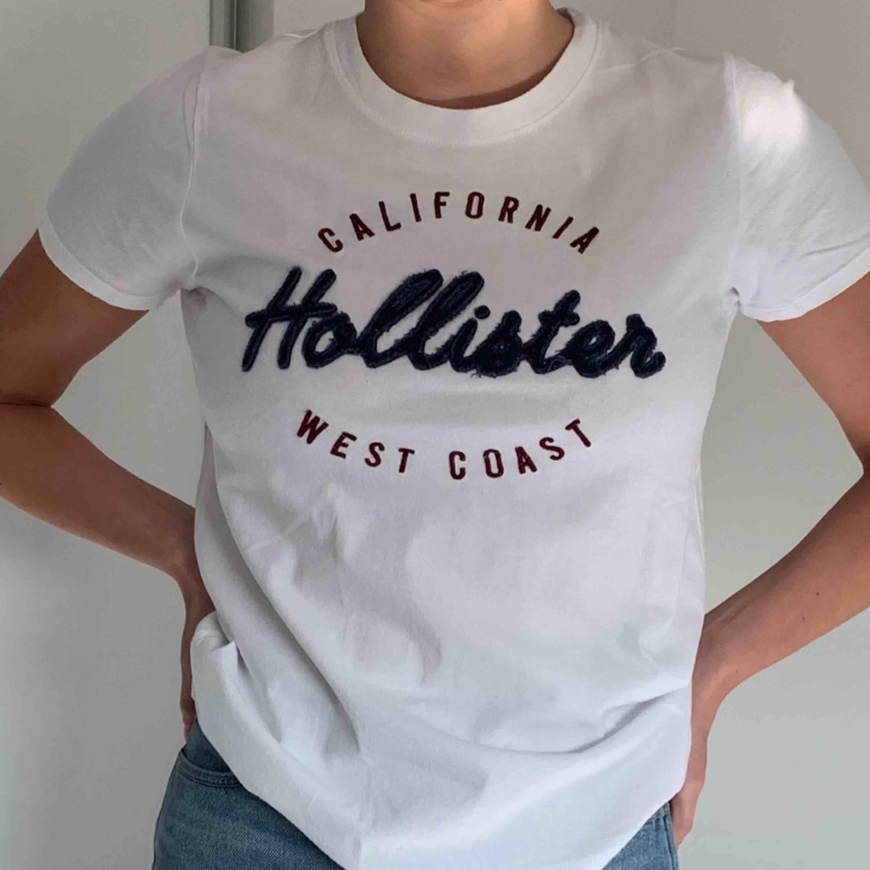 En härlig vit Hollister t-shirt! Har aldrig använt!! (Frakt tillkommer). T-shirts.