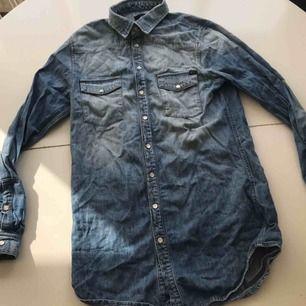 Lång jeansskjorta från Tiger of Sweden. Ljusblå med pärlemorknappar. Bra begagnat skick. Inköpspris 1599:-.
