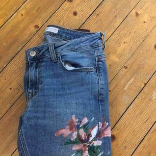 Ett par jeans med ett blommigt tryck på benet. Super fina och sitter jätte fint!