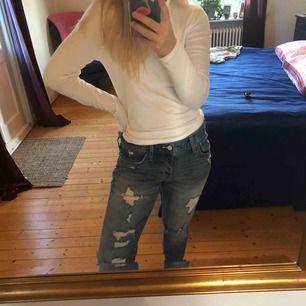 Ett par jeans med slitningar på benen. Bra kvalité knappt använda. Lite oversized men har en väldigt snygg passform.