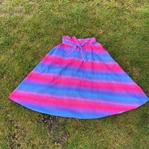 Fantastisk kjol, troligtvis 80-90-tal, färggraderad liksom mellan rosa och lila. Den här liksom riktigt lyser!