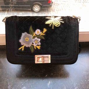 En jättesnygg väska med en blå blomma och ett djur på! Säljer pågrund av att den aldrig använts. Den är perfekt i storleken och har två innefack. Sälja för 150kr plus frakt.