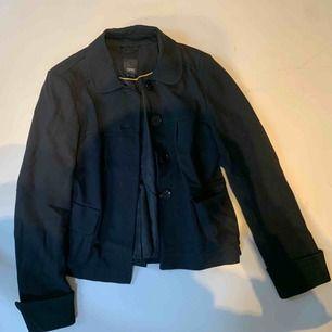 En snygg, stilren, kort, svart kappa. Knappt använd så i väldigt gott skick. Möts på ropsten eller så står köparen för frakten.