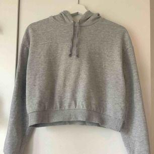 Grå croppad hoodie, slutar vid naveln ungefär. Från H&M. Använd några gånger. Storlek S, 50kr. Frakt tillkommer på 63kr.