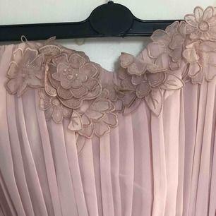 Fin balklänning från hm i gammalrosa färg. Den är axelbandslös o har blomdetaljer upptill. Frakt ingår i priset:)