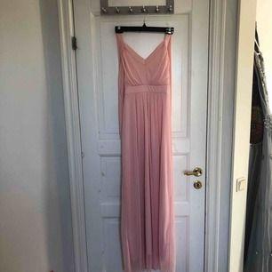 Enkel balklänning i ljusrosa färg. Den är halterneck och är lite nopprig på vissa ställen. Men fortfarande superfin! Frakt ingår i priset:)