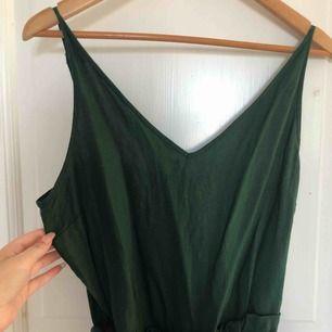 Skön, luftig byxdress från Lindex. Materialet är linne-aktigt och superskön att ha. Snygg mörkgrön färg med knyte i midjan. Frakt ingår i priset!