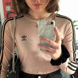 Långärmad Adidas tröja, begie/rosa med svarta ränder. Kort i modellen men den stämmer i storlek. Använd fåtal gånger. Köpt från junkjard