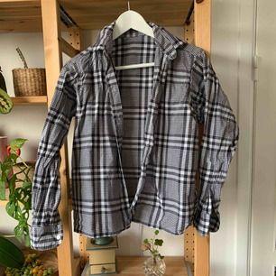 Svartvit rutig skjorta, tippar på storlek 34/36.